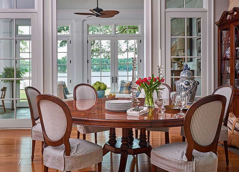 This hamptons wannabe Lake Wylie home with the sunroom in the background, dining room is furnished with new and vintage furnishings, mounted fish and lots of nautical accessories. We slipcovered the lee industrieschair seats to create a more casual, vintage vibe.